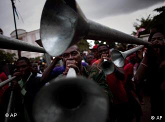 Supporters of Haitian presidential candidate Michel Martelly blow cornets