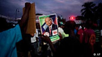 A man holding up a photo of presidential candidate Leslie Voltaire