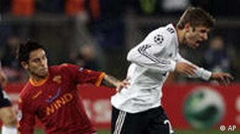 Bayern Munich forward Thomas Mueller is fouled by AS Roma midfielder Leandro Greco