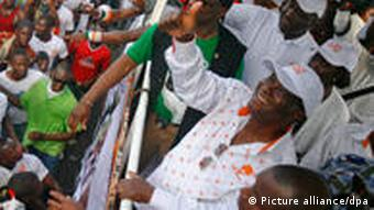Ivory Coast's former prime minister, Alassane Ouattara, waves to supporters