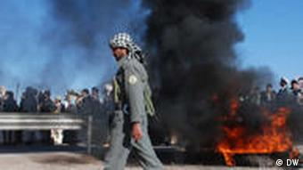 Afghanischer Polizist in Herat neben brennendem Autoreifen Forto:DW