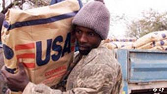 A worker carries relief food from a truck, Saturday Sept. 7, 2002 during food distrubution by the World Food Program in Nhwali in the South Western part of Zimbabwe.