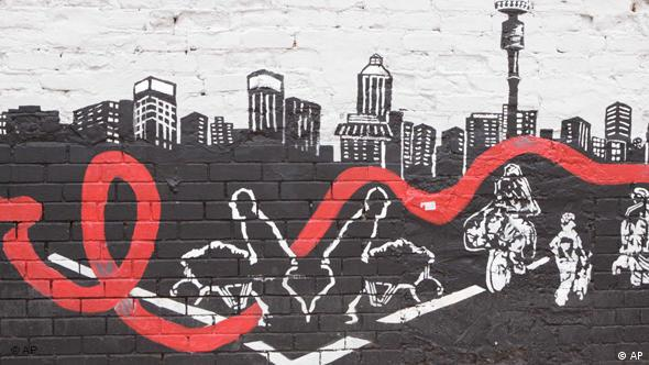 A wall mural in South Africa with the red ribbon that symbolizes the fight against HIV/AIDS running through a cityscape of Johannesburg (AP)