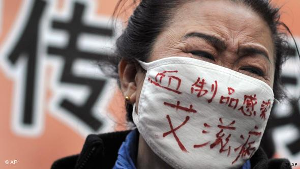 A hemophiliac wearing a face mask bearing the words Blood products infect us with AIDS cries while she with others take center stage during an AIDS awareness event on the World AIDS Day held at the Beijing's south railway station, Tuesday, Dec. 1, 2009. A group of protesters, who has infected HIV from blood transfer products including relatives of the victim disrupted a UNAIDS event, calling for greater support for people living with AIDS/HIV in China. (AP Photo/Andy Wong)