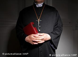 A priest with a cross around his neck and a bible in his hands