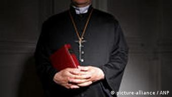 Priest standing with red book
