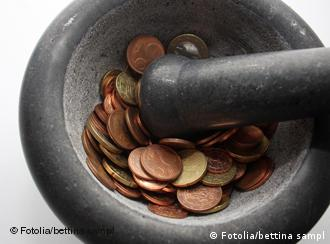 A mortar and pestle grinding euro coins