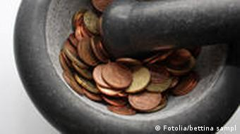A mortar and pestle with coins