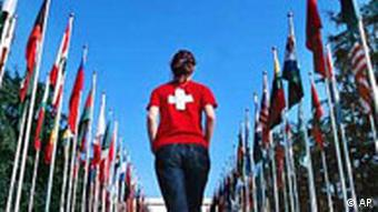 A woman with a Swiss-flag t-shirt walks among flags of other nations