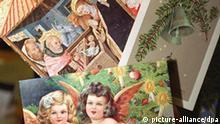 Historische Weihnachtskarten bei einer Ausstellung im Deutschen Postmuseum in Frankfurt (Archivbild vom 28.11.1997). So mancher schreibt sich alljährlich die Finger wund mit Glück- und Segenswünschen zum Weihnachtsfest und Jahreswechsel. Früher hatten es die Menschen einfacher. Man traf sich in der Weihnachtszeit beim Kirchgang und überbrachte die Glückwünsche persönlich. dpa (Zu dpa lhe und lrs 017 vom 17.12.1998)