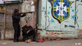 Zwei Polizisten mit Maschinenpistolen suchen Schutz hinter einer Mauer (Foto: AP)