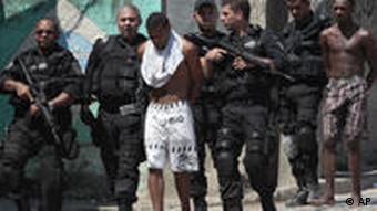 Schwer bewaffnete Polizisten eskortieren Drogendealer, die sie zuvor festgenommen haben (Fott: AP)