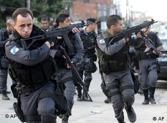 Eine Spezialeinheit der Polizei zielt während des Laufens mit Maschinenpistolen auf ein nicht zu sehendes Ziel (Foto: AP)