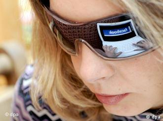 woman's face with facebook reflected in glasses