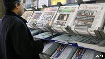 A man looks at a rack of newspapers for sale