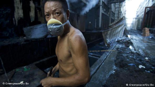 A bare-chested Chinese textile worker wearing a basic face mask (Greenpeace/Qiu Bo)