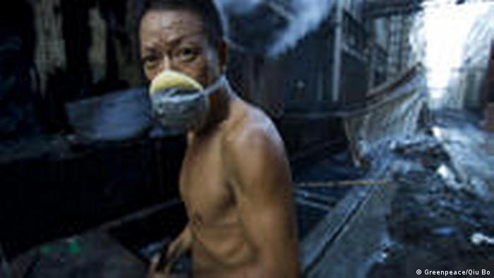 A barechested man wears a face mask to protect against toxins at a denim factory