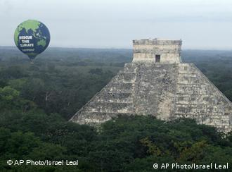 A hot air ballon floating next to a Mayan pyramid carries the words 'Rescue the climate'