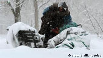 A homeless man seeks shelter in a snowy park