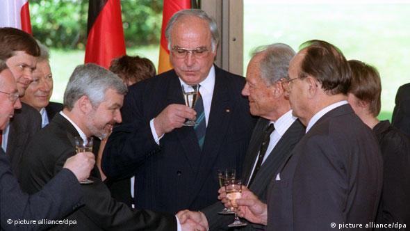 Der polnische Ministerpräsident Krzystof Bielecki (l) und Alt-Bundeskanzler Willy Brandt (SPD) reichen sich nach der Vertragsunterzeichnung die Hände. In der Mitte Bundeskanzler Helmut Kohl (CDU), rechts Bundesaußenminister Hans Dietrich Genscher (FDP). Krzystof Bielecki und Helmut Kohl unterzeichneten am 17. Juni 1991 in Bonn den auf zehn Jahre angelegten Vertrag über gute Nachbarschaft und freundschaftliche Zusammenarbeit. Der Vertrag, sowie das bereits früher unterzeichnete Abkommen zur endgültigen Anerkennung der Oder-Neiße-Linie als polnische Westgrenze, soll nach der Sommerpause vom Bundestag ratifiziert werden.