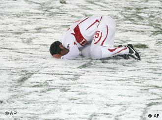 Stuttgart's Elson kneels on the snow covered pitch