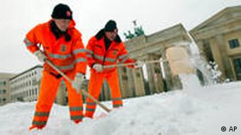 Workers clear the walkway of fresh-fallen snow in front of the Brandenburg Gate in Berlin, Germany