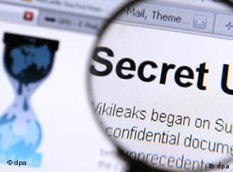 The WikiLeaks site on screen under a magnifying glass