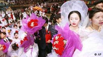 Newly wed couples leave a stadium after a mass wedding in Beijing
