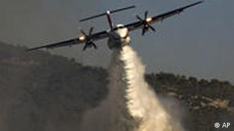 A Russian firefighting plane sprays fire extinguishing material over the fire in Ein Hod, northern Israel, Saturday, Dec. 4, 2010. The cause of the worst forest fire in Israel's history is likely negligence, not arson, authorities said Saturday, as firefighters from around the world battled the blaze whipping through northern pine forests toward the Mediterranean. (AP Photo/Sebastian Scheiner)