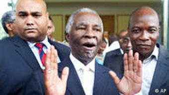Former South African President Thabo Mbeki gestures as he answers reporters.