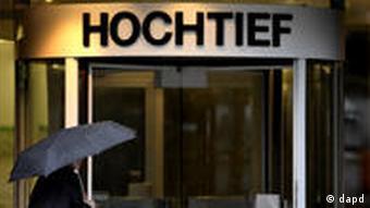 Ein Passant mit Regenschirm geht in Essen an der Zentrale des Baukonzerns Hochtief vorbei (Foto: dapd)