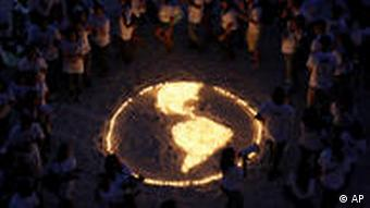 People standing around candles set up to look like a map of the Earth