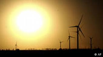 The sun in the background, wind turbines in the foreground