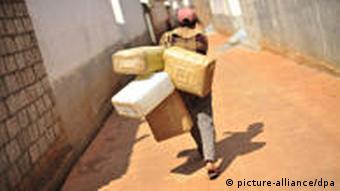 A woman carries empty containers for water