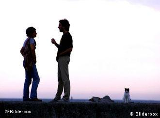 Silhouette of two people in conversation