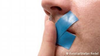 Nahaufnahme Gesicht eins Mannes mit blauem Klebeband auf Mund und Zeigefinger vor den Lippen.(Foto: Stefan Redel)