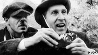 Szene aus Heimat, zwei Männer hintereinander, der erste mit Fotoapparat (Kinowelt)
