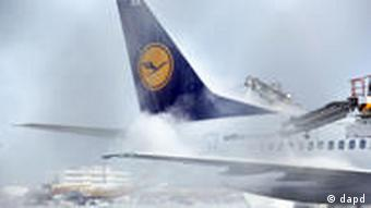 A Lufthansa jet's tail, partially obscured by falling snow