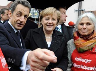Angela Merkel and Nicholas Sarkozy at a crowded Christmas market