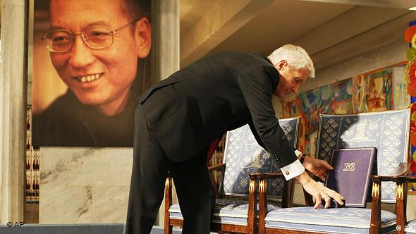 Chairman of the Norwegian Nobel Committee Thorbjoern Jagland places the Nobel diploma and Nobel medal on the empty chair during the ceremony in Oslo City Hall Friday Dec. 10, 2010 to honour in absentia this years Nobel Peace Prize winner, jailed Chinese dissident Liu Xiaobo. (AP Photo Heiko Junge, pool)