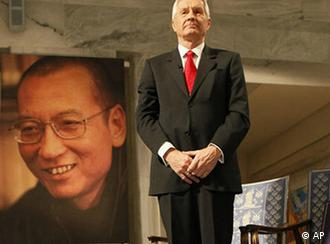 Chairman of the Norwegian Nobel Committee Thorbjoern Jagland poses next to  the Nobel diploma and Nobel medal placed on the empty chair during the ceremony in Oslo City Hall Friday Dec. 10, 2010 to honour in absentia this years Nobel Peace Prize winner, jailed Chinese dissident Liu Xiaobo.  (AP Photo Heiko Junge, pool)