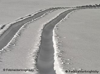 Tracks through the snow lead off to the horizon