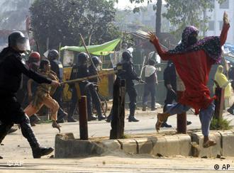 Ein Polizist rennt mit einem Schlagstock hinter einem protestierenden Mann hinterher (Foto: AP)