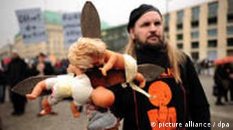 A protester in Berlin in 2010, holding dolls