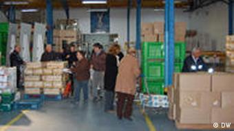 Helfer verladen Essensspenden im Lager der Nahrungsmittelbank in Lissabon (Foto: DW)