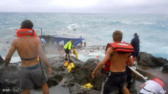 People clamber on the rocky shore on Christmas Island during a rescue attempt as a boat breaks up in the background Wednesday, Dec. 15, 2010. A wooden boat packed with dozens of asylum seekers smashed apart on cliff-side rocks in heavy seas off an Australian island