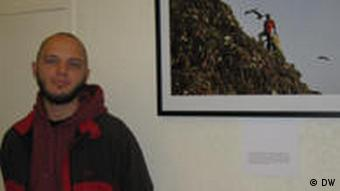 Photographer Enrico Fabian stands next to one of his pictures at the Berlin gallery