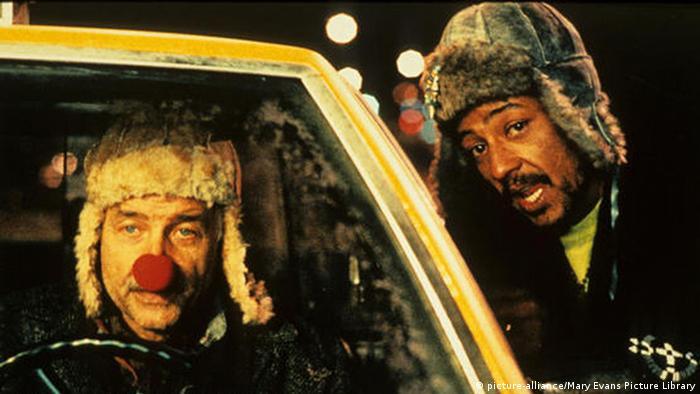 Filmstill aus Night on Earth - Armin Mueller-Stahl sitzt mit roter Nase hinter dem Lenkrad eines Taxis; sein nächster Fahrgast, Yoyo (Giancarlo Esposito), spricht mit ihm durchs Fenster