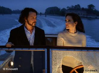 Angelina Jolie und Johnny Depp unterhalten sich in einer Szene auf einem Motorboot (Foto: Kinowelt)