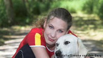 Eine Frau hält einen Hund umarmt